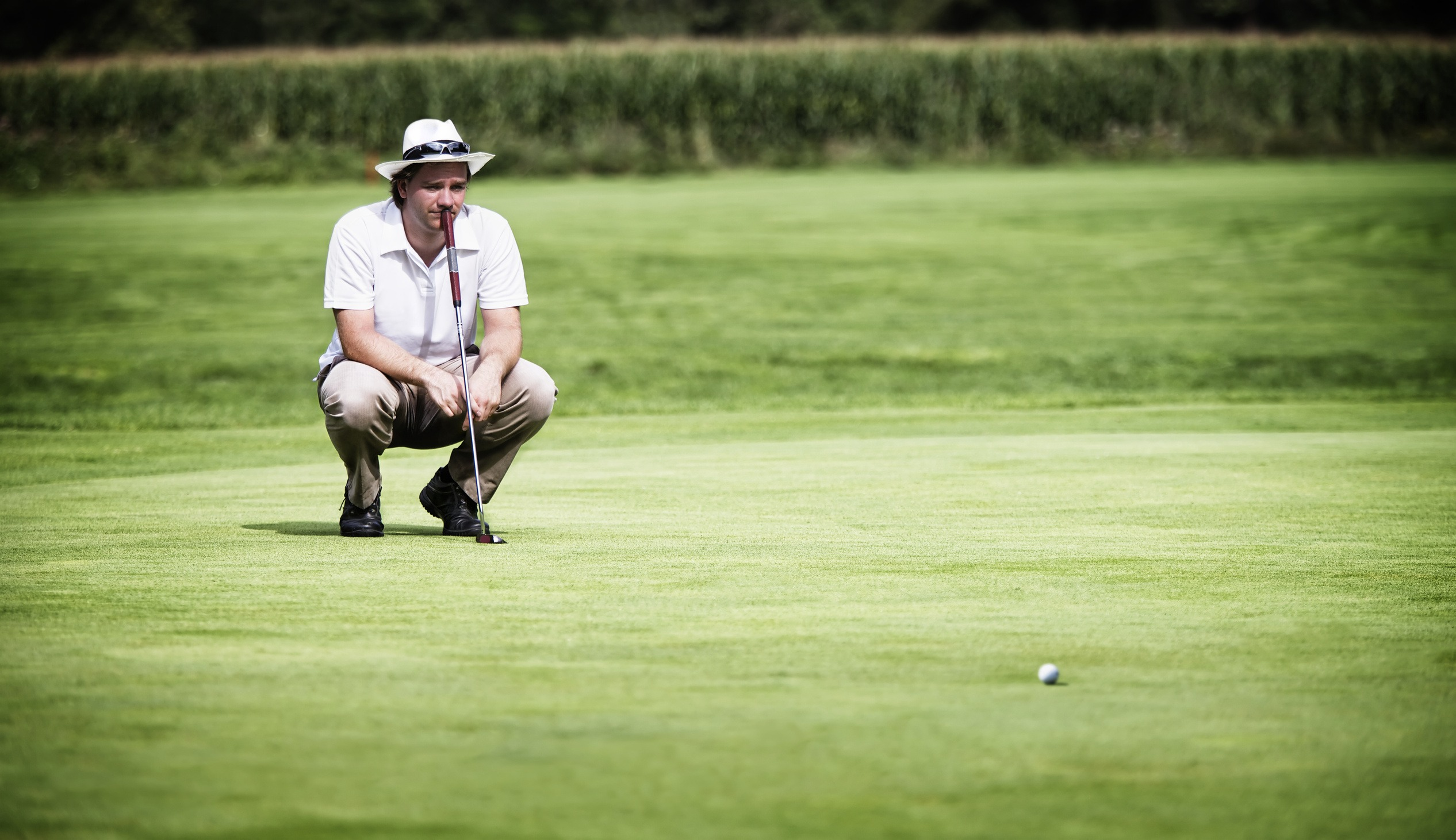 Young male golf player with putter squatting to study the green at golf course.